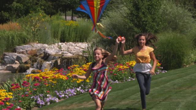 stockvideo's en b-roll-footage met slo mo ms two sisters (12-13, 16-17) running with kites in park / utah, usa - 12 13 jaar