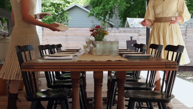 vidéos et rushes de ms two sisters setting table for dinner on front porch of home - prendre son repas