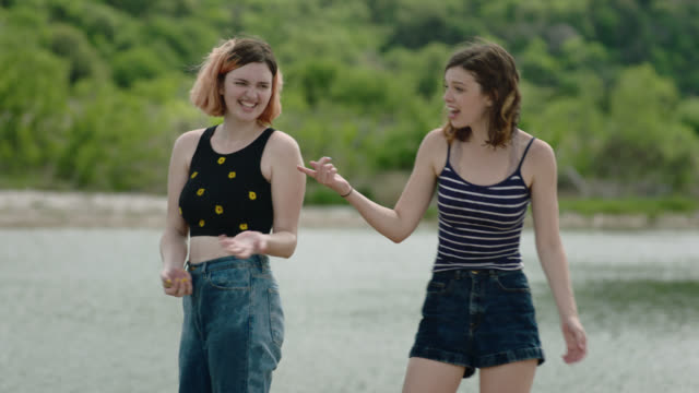 MS. Two sisters skip stones across river in state park.