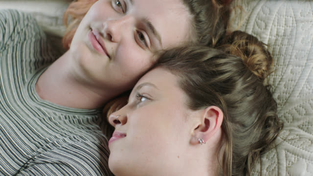 CU SLO MO. Two sisters snuggle and laugh together on bed.