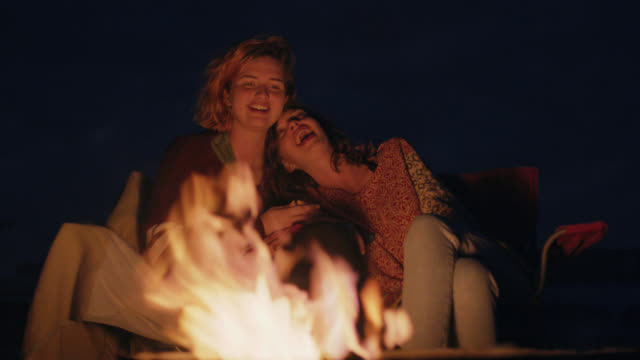 ws. two sisters talk and laugh by fire pit on camping trip. - fuoco di accampamento video stock e b–roll