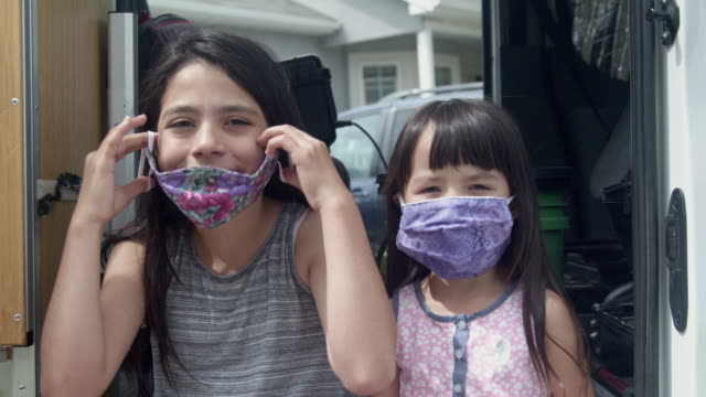 two sisters, the oldest helping the youngest put on her covid-19 mask - applying stock videos & royalty-free footage