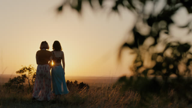 WS SLO MO. Two sisters walk hand in hand through mountain field at sunset and look out over valley.