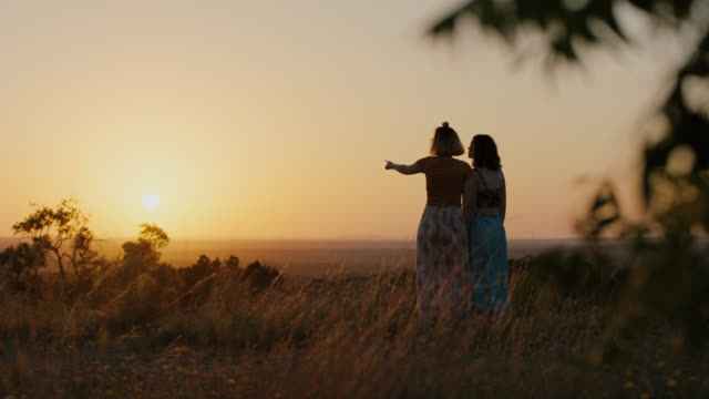 WS SLO MO. Two sisters walk with fingers linked through mountain field at sunset and look out over valley.
