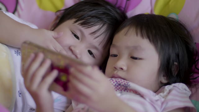 Two Sisters Watching A Movie On Smart Phone