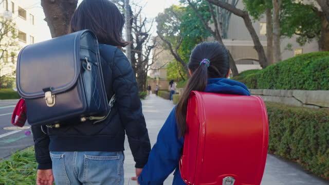 保護フェイスマスクを着用し、一緒に学校に歩いている2人の姉妹 - 新学期点の映像素材/bロール