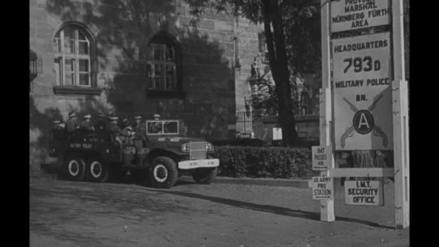 two sixwheeled american vehicles at door with sign provost marshall members [furthy] area headquarters 793d military police a lmt security office /... - processi di norimberga video stock e b–roll