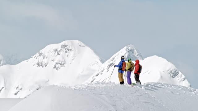 ld zwei skifahrer und ein snowboarder genießen den blick vom berggipfel - skibrille stock-videos und b-roll-filmmaterial