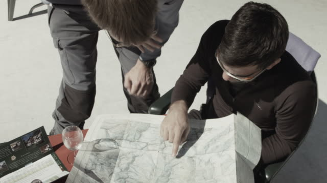 Two skiers at hut in Swiss Alps studying topographic map