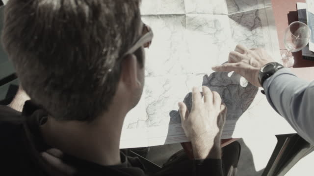 two skiers at hut in swiss alps studying topographic map - たたむ点の映像素材/bロール