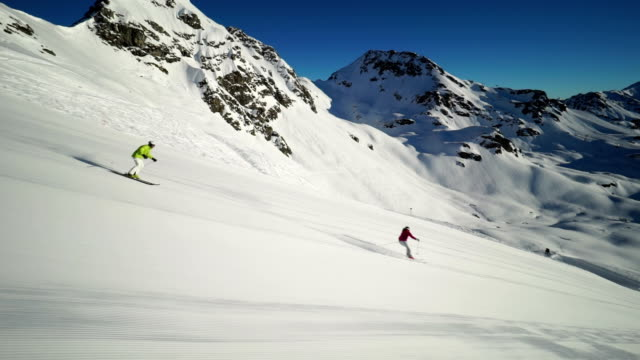 two skiers carving on empty ski piste - ski jacket stock videos and b-roll footage