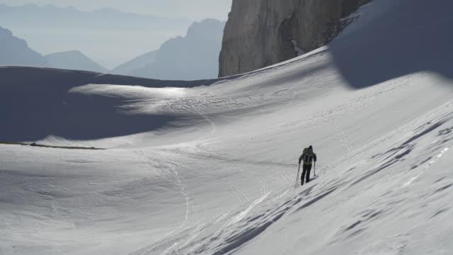 two skiers cross country skiing up a mountain. - längd bildbanksvideor och videomaterial från bakom kulisserna
