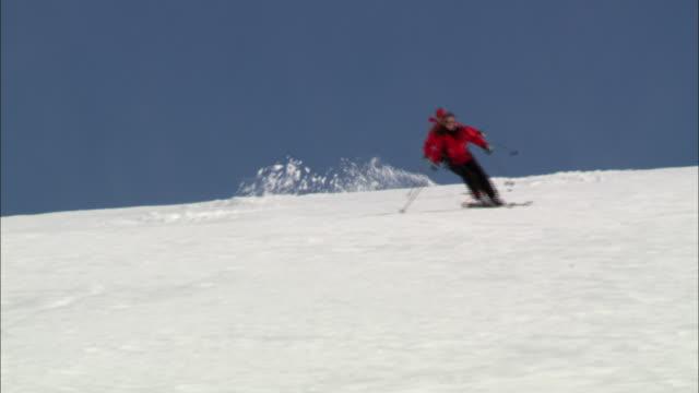 vídeos y material grabado en eventos de stock de two skiers descend a slope along the cariboo and monashee mountains. - vacaciones en la nieve