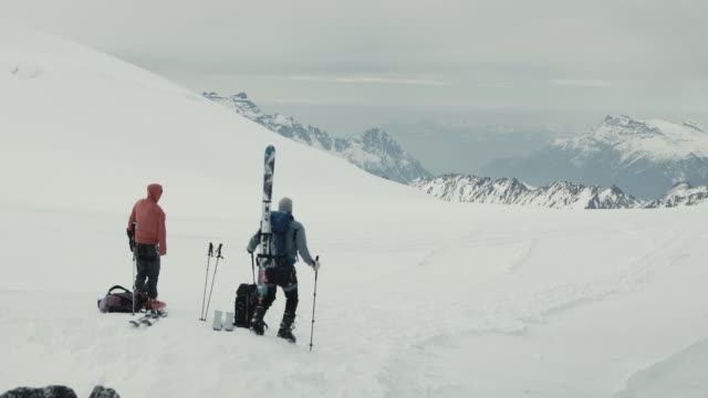 vidéos et rushes de two skiers getting ready, pointing a mountain range in the snow - amitié masculine