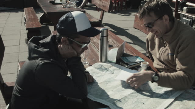Two Skiers planning route, looking at map at hut in Swiss Alps