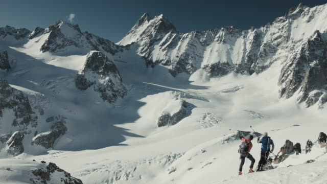 Two skiers pointing at mountain tops with ski poles, discussion plans in Swiss Alps