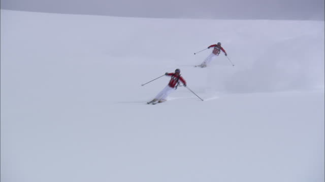 two skiers race down a snowy slope. - downhill skiing stock videos & royalty-free footage