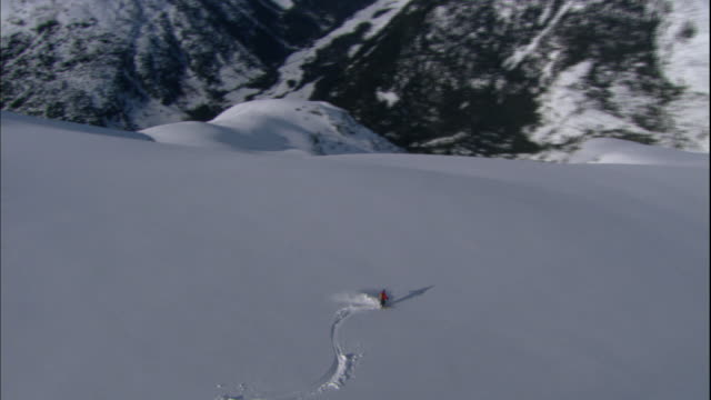 two skiers traverse a steep mountainside. - rocky mountains stock videos & royalty-free footage