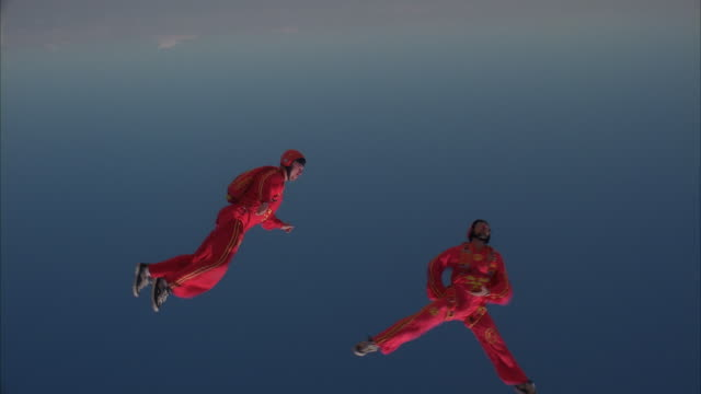 Two skydivers dressed in red jumpsuits exit the plane and fly around eachother.