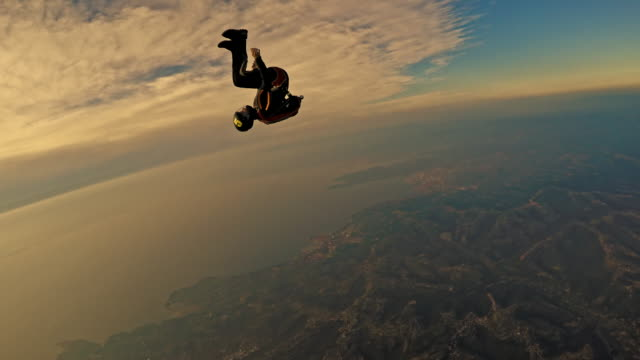 pov two skydivers enjoying in air over coastline at sunset - free falling stock videos & royalty-free footage