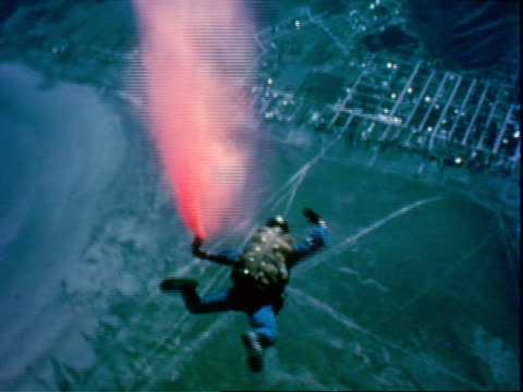 vidéos et rushes de two skydivers freefalling /skydiver dispersing red powdery material while freefalling / small plane and diver freefalling pan to aerial of ground... - répandre