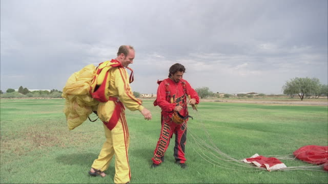 two skydivers high five after landing and gather up their parachutes. - パラシュート点の映像素材/bロール