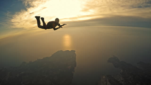 pov two skydivers in air as sun sets behind sea - skydiving stock videos & royalty-free footage