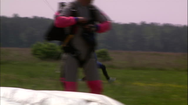 two skydivers land on the ground and run a bit as they get their feet back under them. - under her feet stock videos & royalty-free footage