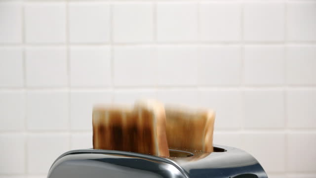 Two slices of toast popping up from toaster
