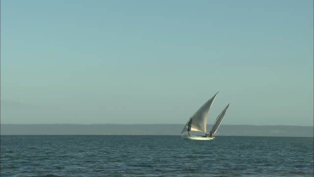 two small boats sail across the zambezi river delta.  - ダウ船点の映像素材/bロール