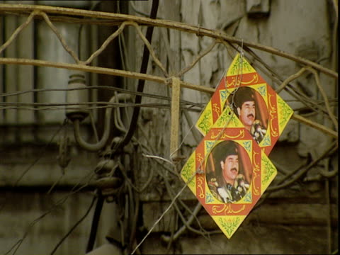 vídeos de stock, filmes e b-roll de two small diamond shaped images of saddam hussein attached to metal archway / baghdad, iraq - figura masculina