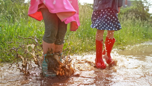 slo mo two small girl jumping in a muddy puddle and smiling - wellington boot stock videos & royalty-free footage