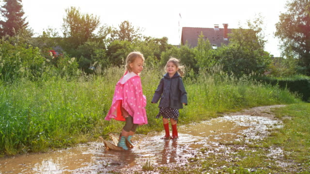 ld two small girls jumping up and down in a muddy puddle wearing rain boots and coats - puddle stock videos & royalty-free footage