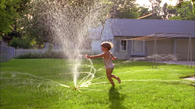 vídeos de stock, filmes e b-roll de two small  girls wearing swimsuits run through a backyard sprinkler. - aspersor