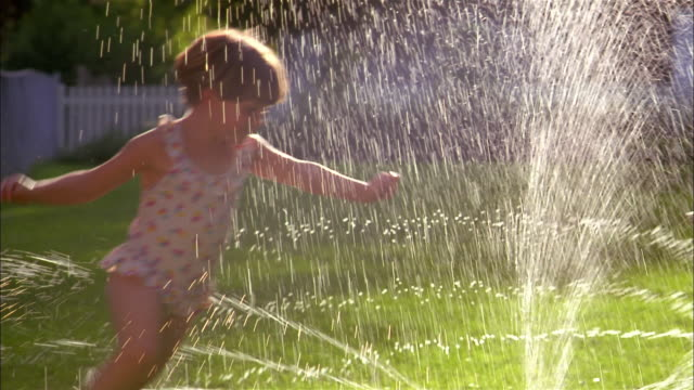 Two small  girls wearing swimsuits run through a backyard sprinkler.