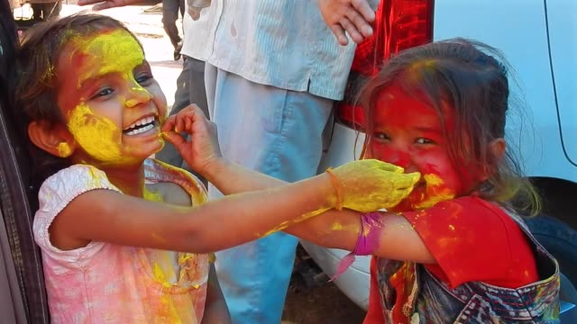 stockvideo's en b-roll-footage met two small kid girls putting colours on each other's faces / lathmar holi celebrations in the village of barsana on march 17 2016 holi or the festival... - holi phagwa