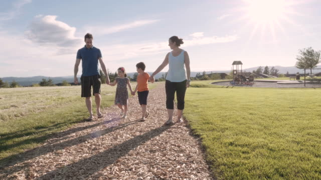 two small kids and their parents out for a walk - playground stock videos & royalty-free footage