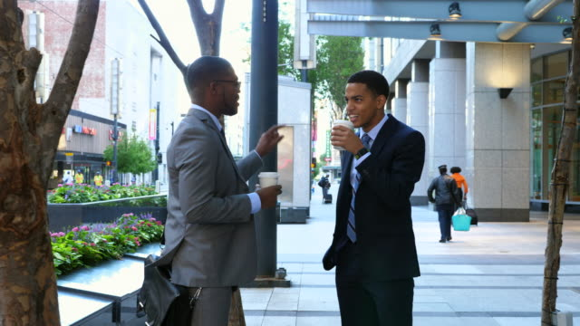 MS TS Two smiling businessmen in discussion while walking on city sidewalk