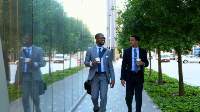 MS Two smiling businessmen in discussion while walking on city sidewalk