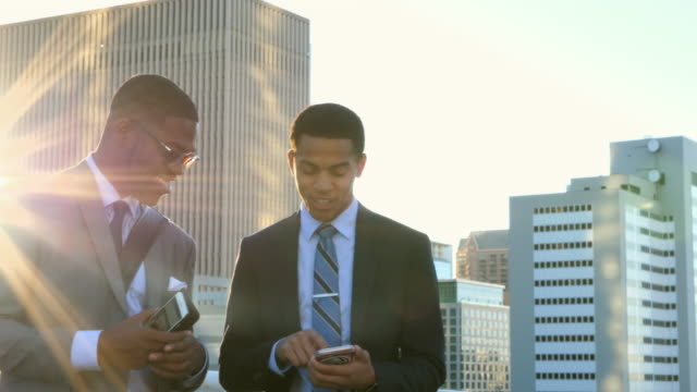 MS Two smiling businessmen standing on parking garage rooftop looking at smartphone