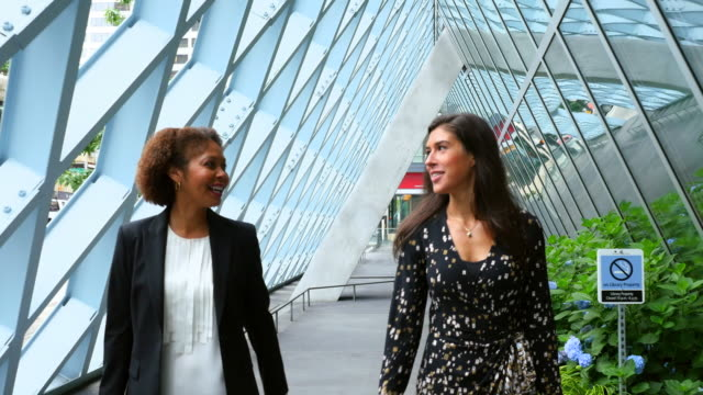 MS TS Two smiling businesswomen in discussion while walking down corridor outside of office building