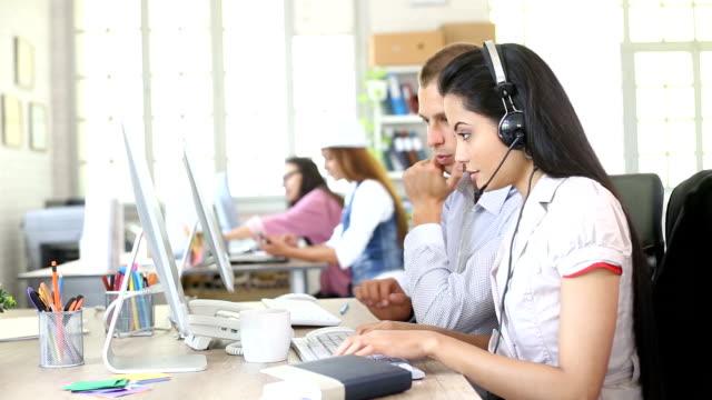 Zwei lächelnde Mitarbeiter arbeiten an Computern im modernen Büro