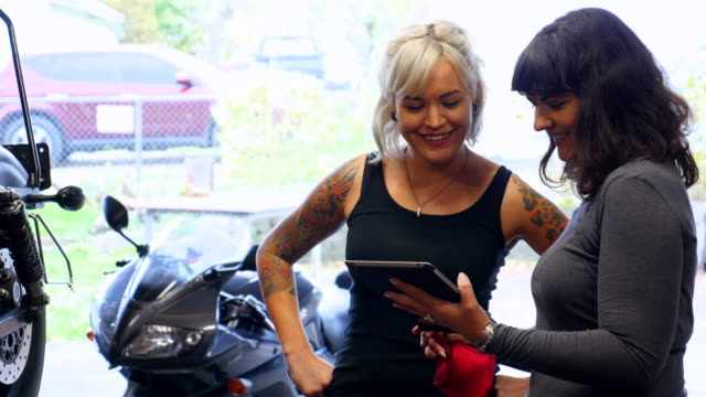 two smiling female mechanics working on motorcycle in garage reading manual on digital tablet - sleeve stock videos & royalty-free footage