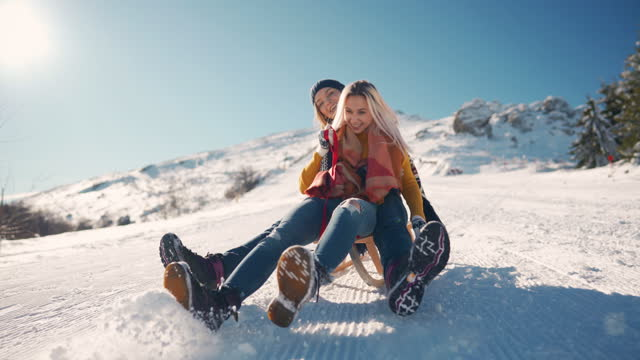 two smiling girlfriends sledding down the snowy mountain together and having fun - sledge stock videos & royalty-free footage