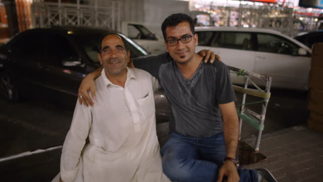 two smiling middle eastern/indian men laugh and joke around - deira, dubai - vereinigte arabische emirate stock-videos und b-roll-filmmaterial