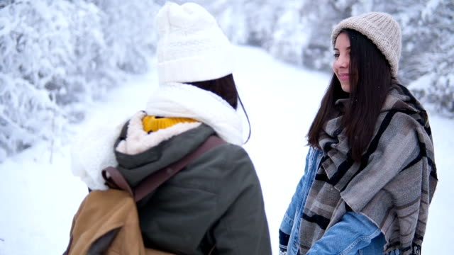 Two smiling women are walking in the park in winter. Friends with backpacks go through the forest. Girls in knitted hats and winter jackets against the background of a snowy forest.