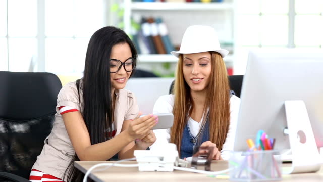 vídeos y material grabado en eventos de stock de dos sonrientes mujeres hablando y usando el teléfono inteligente en lugar de trabajo - narrar