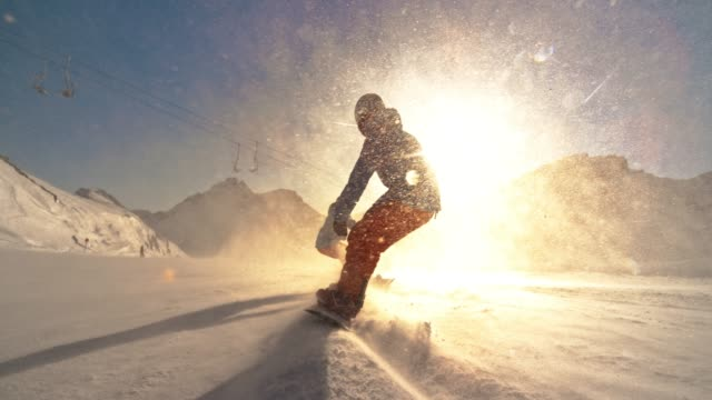 slo mo ts two snowboard riders riding down the mountain slope towards the setting sun - sports equipment stock videos & royalty-free footage