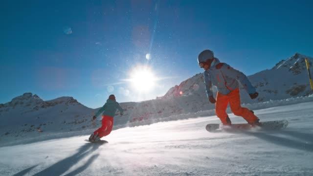 vidéos et rushes de slo mots deux snowboarders descendant la montagne sur un sentier ensoleillé - exactitude