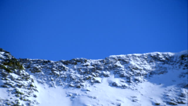 vídeos de stock, filmes e b-roll de two snowboarders jumping in front of blue sky - forma da água